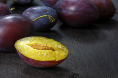 Purple plums whole and half on dark brown wood, closeup Royalty Free Stock Images