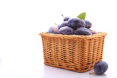 Purple plums. In a wicker basket on a white background royalty free stock image