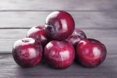 Purple plums, on wooden background. Ripe purple plums, on wooden background Royalty Free Stock Photography