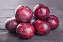 Purple plums, on wooden background. Ripe purple plums, on wooden background Royalty Free Stock Image