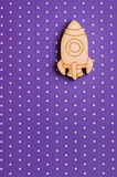 Purple polka dot desk with wooden space ship Stock Image