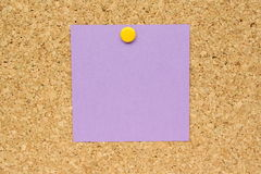 Purple Post It Note. Purple square post it note and yellow pin on a cork board stock images