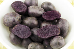 Purple Potatoes. White bowl full of very dark fleshed tuber vegetables Stock Photo