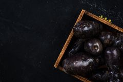 Purple potatoes in wooden crate Stock Photo