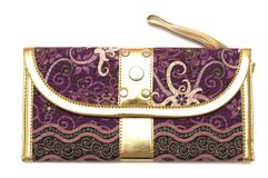 A purple pouch with zipper puller. A side view photo taken on a purple gold rimmed pouch with zipper puller hand strap against a white backdrop Stock Image