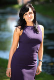 Purple pretty woman. Pretty dark haired woman with a purple dress is standing in front of a nice lake. the background is blurred. The woman is smiling Royalty Free Stock Images