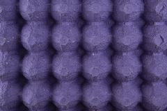 Purple protective tray for raw chicken eggs with cells, full frame. Close up royalty free stock photo