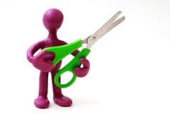 Purple puppet of plasticine holding green scissors royalty free stock photos