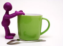 Purple puppet of plasticine rest on cup Royalty Free Stock Image