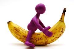 Purple puppet of plasticine riding on banana Stock Photography