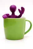 Purple puppet of plasticine signing from cup Stock Image