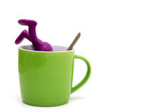 Purple puppet of plasticine sinking in cup Stock Photography