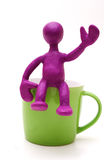 Purple puppet of plasticine sitting on cup Stock Image