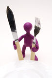 Purple puppet of plasticine standing behind plate Royalty Free Stock Photo