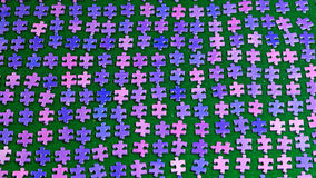 Purple puzzle pieces sorted on a green table cloth Royalty Free Stock Images