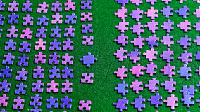 Purple puzzle pieces sorted on a green table cloth Stock Photos