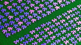 Purple puzzle pieces sorted on a green table cloth Stock Images