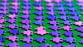 Purple puzzle pieces sorted on a green table cloth Stock Photo