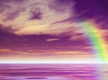 Purple Rainbow. Rainbow rips across a purple sea and purple sky Royalty Free Stock Image