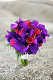 Purple and red flowers wedding bouquet on the beach Stock Photos