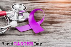 Purple ribbon awareness and stethoscope on wooden background. For World Cancer day campaign stock photos
