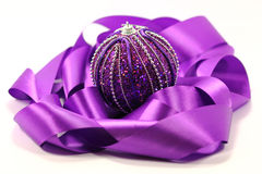 Purple ribbon and ball. Purple ribbon and the new years purple ball with glitter on a white background Royalty Free Stock Photography