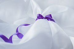 Purple ribbon with bow on a white cloth Stock Photos