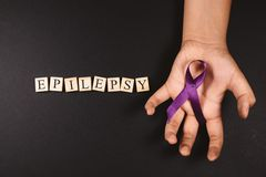 Purple ribbon on cramps hand and EPILEPSY word against black background.