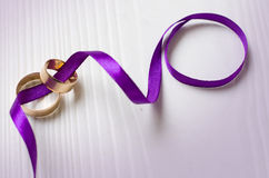 Purple ribbon and wedding rings Stock Photography