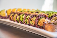 Purple rice sushi roll with mango and avocado for a vegan sushi meal. Purple rice sushi roll with mango and avocado for a Japanese vegan sushi meal Stock Photos
