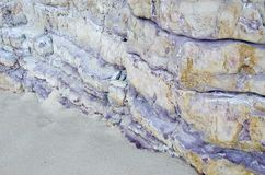 The purple rock on the beach. The purple dissected rock, Sagres, Spain Royalty Free Stock Image