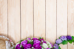 Purple roses hat on wooden background. Top view. Stock Photo
