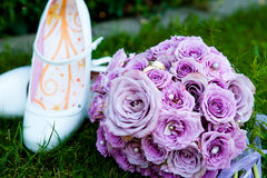 Purple roses wedding. Purple bouquet of violet roses is laying down on the meadow in the grass. beside are white plateau wedding shoes of the bridal stock image
