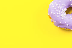 Purple round donut on yellow background. Flat lay, top view. Royalty Free Stock Image