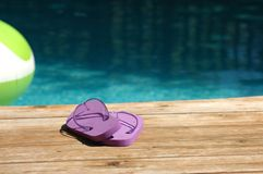 Purple sandles at pool. Purple sandles on a deck poolside Royalty Free Stock Image
