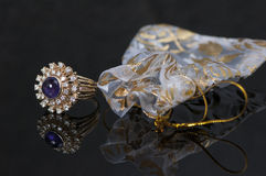 Purple sapphire ring with diamonds. Purple ring is vintage and has several diamonds surrounding the stone. The ring setting is gold and there is gold and white Stock Image