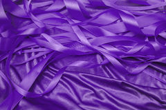 Purple satin ribbons. In a messy mess texture background Stock Photos