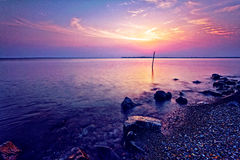 Purple Sea. With a glistening red sun in the horizon Royalty Free Stock Photography