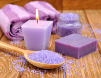 Purple sea salt and a burning candle Royalty Free Stock Photography