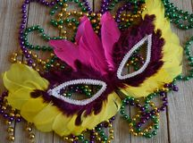 Mardi Gras mask with beads on a wood background. Purple sequin carnival mask with a string of colorful beads stock images