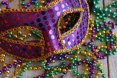 Mardi Gras mask with beads on a wood background. Purple sequin carnival mask with a string of colorful beads royalty free stock photos