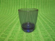 Purple Shot Glass by Kambas. Plastic purple shot glass 25ml on a green table cloth background Stock Photo