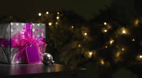 Purple and silver wrapped christmas present with tree Royalty Free Stock Photo