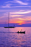Purple sky with boat and sailing ship silhouette Royalty Free Stock Photography