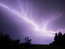 Lightning in purple sky. Purple sky with a huge lightning bolt diagonally across sky at night stock photo