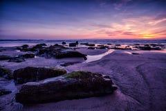 Purple sky sunset on rocky coast beach. Stunning coastal scene in Cornwall, England Royalty Free Stock Images