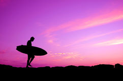 Purple Sky Surfer. Vacation Silhouette Of A Surfer Carrying His Board Against A Purple Sunset Stock Photo