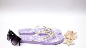 Purple slippers and sunglasses and sea shell on white background - Stop motion stock footage