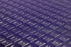 Purple small embossed squares on purple background stock photography