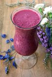 Purple smoothie with blue and white flower Stock Photo